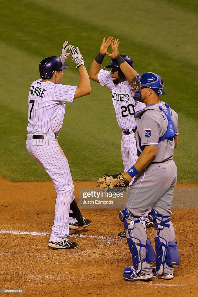 Matt McBride #7 of the Colorado Rockies celebrates his sixth-inning grand slam with <a gi-track='captionPersonalityLinkClicked' href=/galleries/search?phrase=Wilin+Rosario&family=editorial&specificpeople=5734314 ng-click='$event.stopPropagation()'>Wilin Rosario</a> #20 as catcher <a gi-track='captionPersonalityLinkClicked' href=/galleries/search?phrase=Erik+Kratz&family=editorial&specificpeople=809194 ng-click='$event.stopPropagation()'>Erik Kratz</a> #19 of the Kansas City Royals looks on at Coors Field on August 20, 2014 in Denver, Colorado. The Rockies defeated the Royals 5-2.