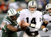 Matt McGloin of the Oakland Raiders is sacked by Calvin Pace of the New York Jets during the fourth quarter at MetLife Stadium on December 8 2013 in...