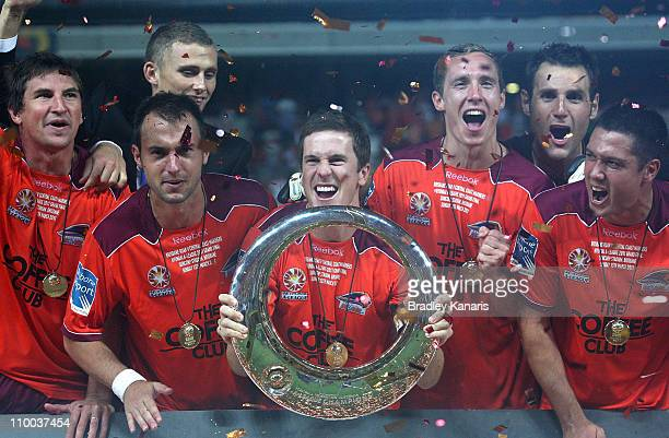 Matt McKay of the Roar holds the winners trophy as he celebrates victory with team mates after the ALeague Grand Final match between the Brisbane...