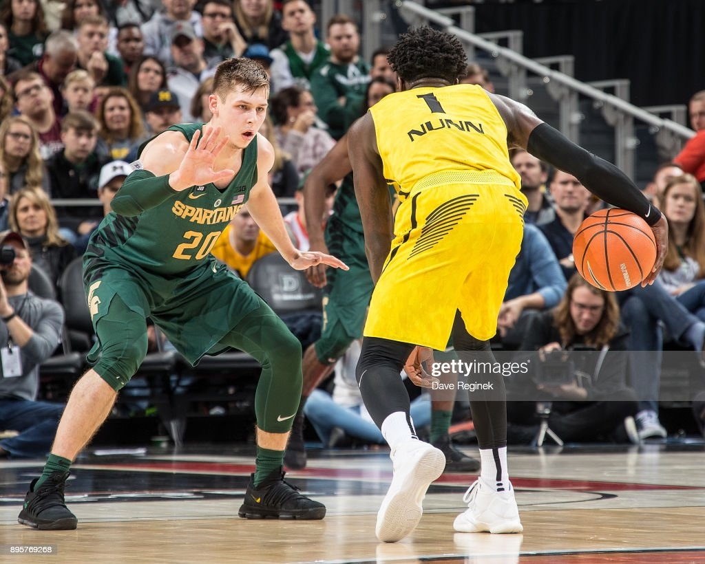 Matt McQuaid #20 of the Michigan State Spartans defends against Kendrick Nunn #1 of the Oakland Golden Grizzlies during game two of the Hitachi College Basketball Showcase at Little Caesars Arena on December 16, 2017 in Detroit, Michigan. The Spartans defeated the Grizzles 86-73.