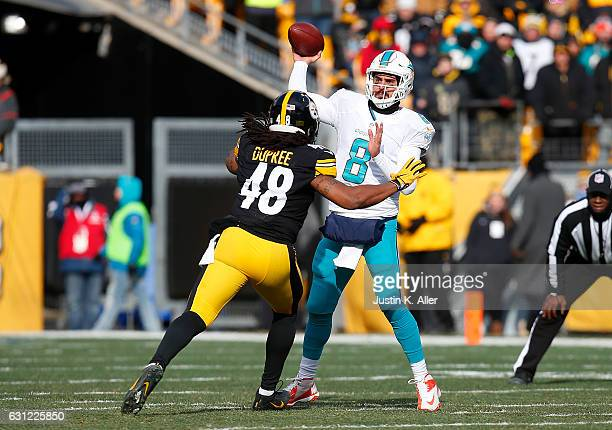 Matt Moore of the Miami Dolphins attempts a pass while under pressure from Bud Dupree of the Pittsburgh Steelers in the first quarter during the Wild...