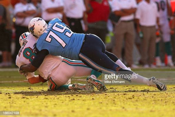 Matt Moore of the Miami Dolphins is sacked by Jarius Wynn of the Tennessee Titans during a game at Sun Life Stadium on November 11 2012 in Miami...