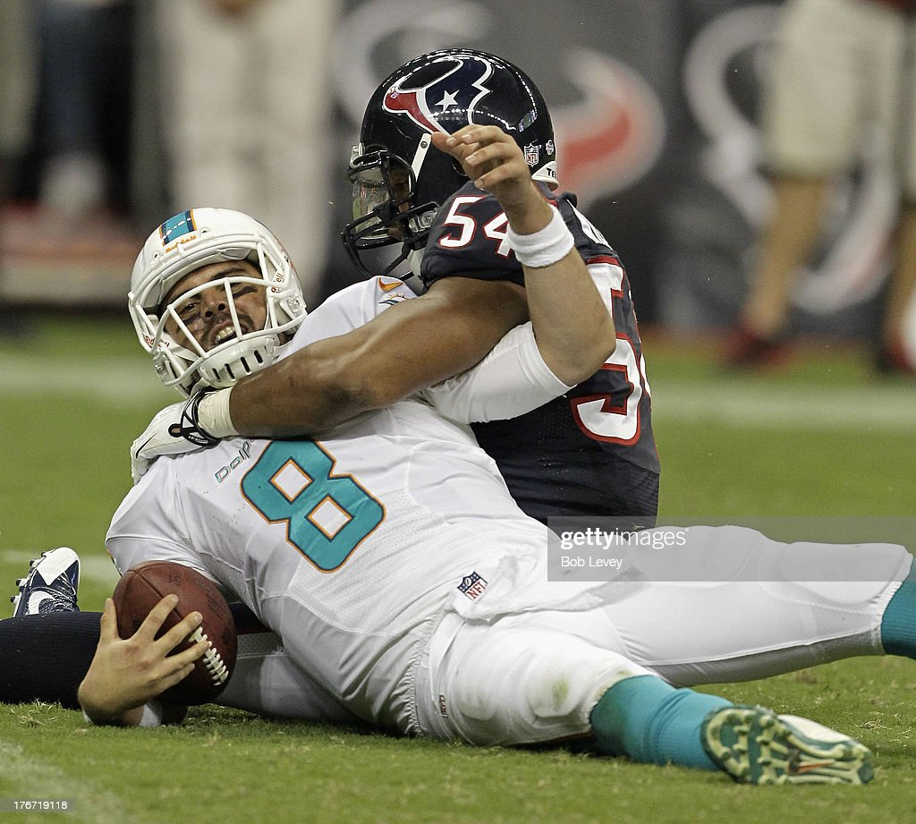 Matt Moore #8 of the Miami Dolphins is sacked by Trevardo Williams #54 of the Houston Texans at Reliant Stadium on August 17, 2013 in Houston, Texas.