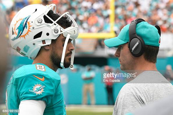 Matt Moore of the Miami Dolphins talks to Head Coach Adam Gase of the Miami Dolphins during a timeout of the game against the New England Patriots at...