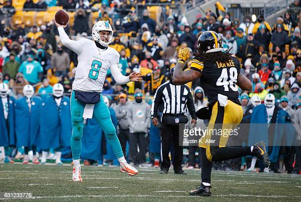 Matt Moore of the Miami Dolphins throws a 4 yard touchdown pass to Damien Williams of the Miami Dolphins against the pressure of Bud Dupree of the...