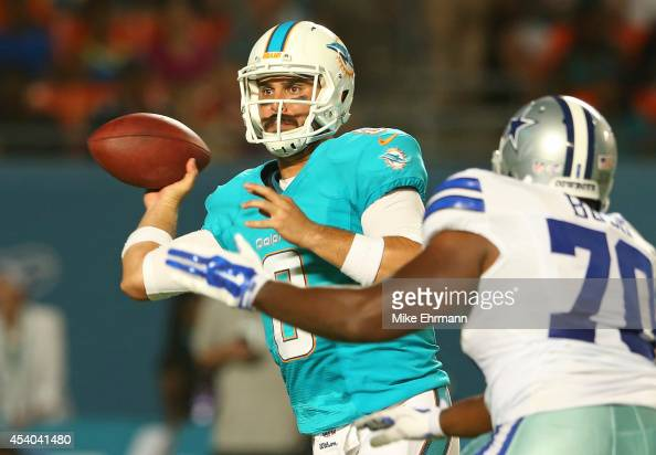 Matt Moore of the Miami Dolphins throws under pressure from Dartwan Bush of the Dallas Cowboys during a preseason game at Sun Life Stadium on August...