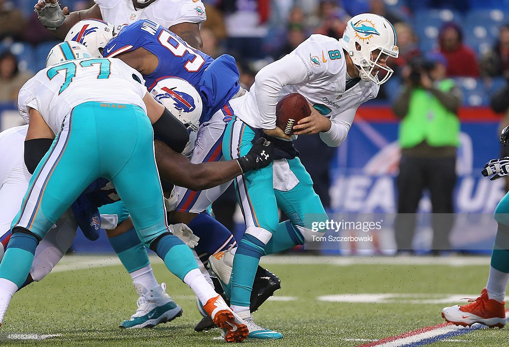 Matt Moore #8 of the Miami Dolphins tries to get away as he is stopped in the pocket during NFL game action against the Buffalo Bills at Ralph Wilson Stadium on December 22, 2013 in Orchard Park, New York.