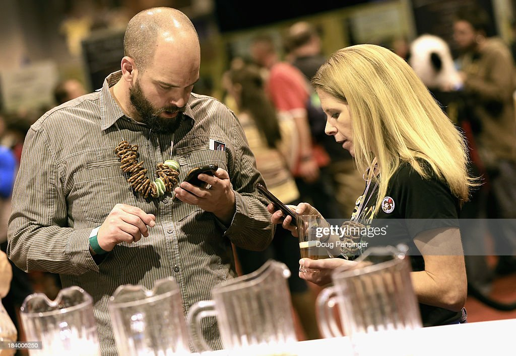 Matt Morris and Mikki Roth of Denver, Colorado use the official GABF app to take notes and track the beers they taste at the 32nd annual Great American Beer Festival at the Colorado Convention Center on October 10, 2013 in Denver, Colorado. The GABF runs October 10-12 and 49,000 attendees will be offered 3100 beers from 624 breweries.
