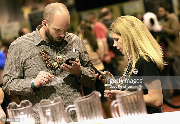 Matt Morris and Mikki Roth of Denver Colorado use the official GABF app to take notes and track the beers they taste at the 32nd annual Great...