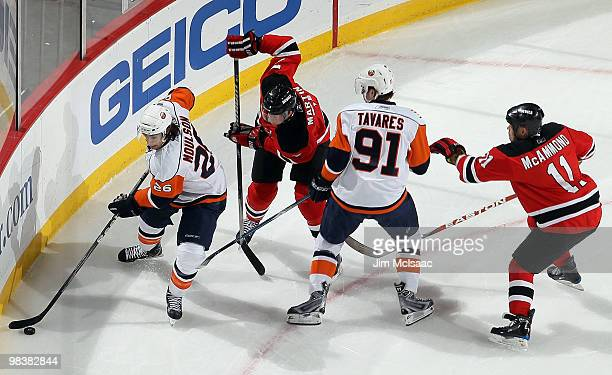 Matt Moulson and John Tavares of the New York Islanders control the puck against Paul Martin and Dean McAmmond of the New Jersey Devils at the...