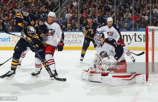 Matt Moulson of the Buffalo Sabres is defended by Joonas Korpisalo and Cam Atkinson of the Columbus Blue Jackets during an NHL game at the KeyBank...