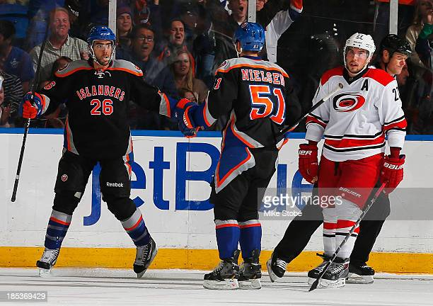Matt Moulson of the New York Islanders celebrates his 2nd period goal with teammate Frans Nielsen as Justin Faulk of the Carolina Hurricanes looks on...