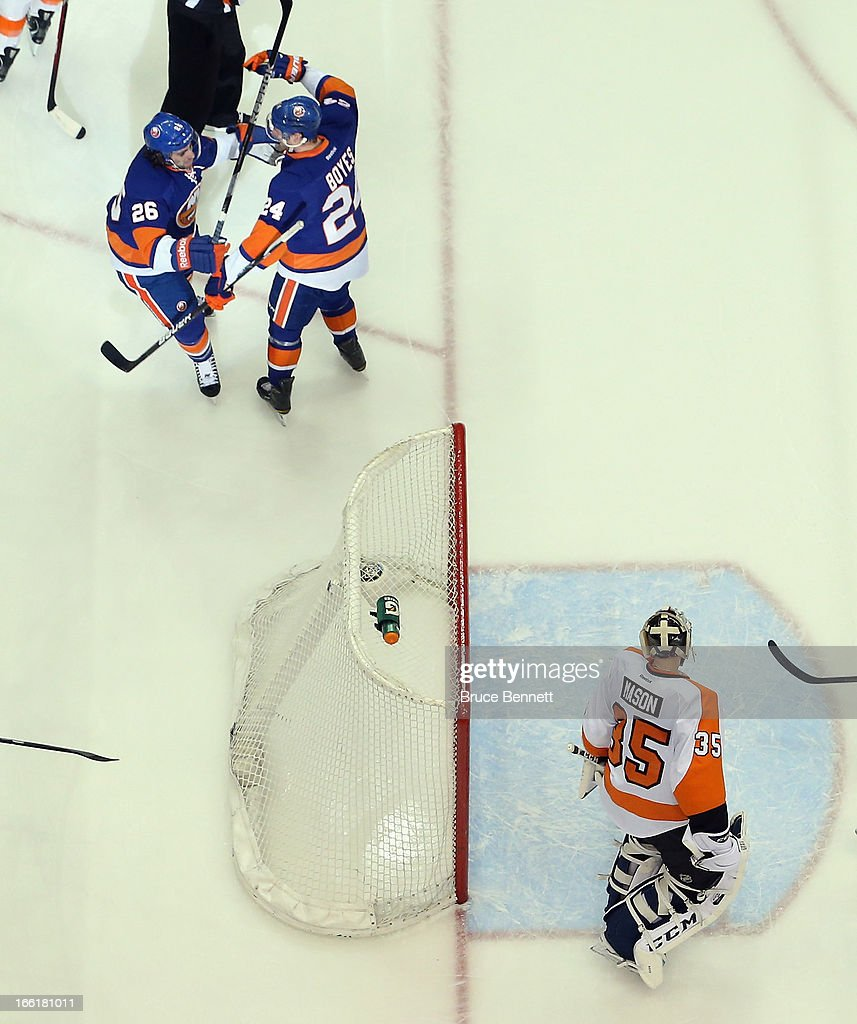 Matt Moulson #26 (L) of the New York Islanders celebrates his goal at 15:36 of the first period against Steve Mason #35 of the Philadelphia Flyers along with Brad Boyes #24 (R) at the Nassau Veterans Memorial Coliseum on April 9, 2013 in Uniondale, New York. The Islanders defeated the Flyers 4-1.