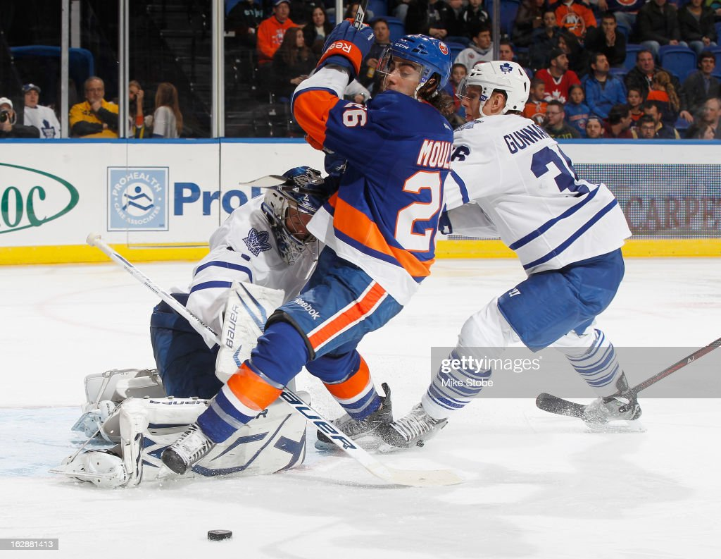 <a gi-track='captionPersonalityLinkClicked' href=/galleries/search?phrase=Matt+Moulson&family=editorial&specificpeople=3365493 ng-click='$event.stopPropagation()'>Matt Moulson</a> #26 of the New York Islanders collides with James Reimer #34 and <a gi-track='captionPersonalityLinkClicked' href=/galleries/search?phrase=Carl+Gunnarsson&family=editorial&specificpeople=5557315 ng-click='$event.stopPropagation()'>Carl Gunnarsson</a> #36 of the Toronto Maple Leafs at Nassau Veterans Memorial Coliseum on February 28, 2013 in Uniondale, New York. The Maple Leafs defeated the Islanders 5-4 in overtime.