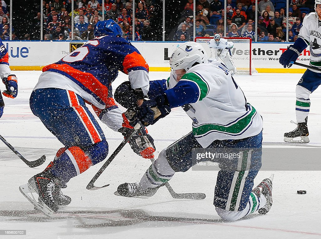 <a gi-track='captionPersonalityLinkClicked' href=/galleries/search?phrase=Matt+Moulson&family=editorial&specificpeople=3365493 ng-click='$event.stopPropagation()'>Matt Moulson</a> #26 of the New York Islanders collides with <a gi-track='captionPersonalityLinkClicked' href=/galleries/search?phrase=Mike+Santorelli&family=editorial&specificpeople=4517042 ng-click='$event.stopPropagation()'>Mike Santorelli</a> #25 of the Vancouver Canucks at Nassau Veterans Memorial Coliseum on October 22, 2013 in Uniondale, New York. The Canucks defeated the Islanders 5-4 in overtime.