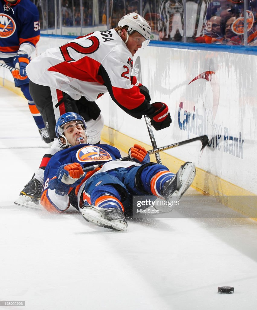 Matt Moulson #26 of the New York Islanders is knocked to the ice by Erik Condra #22 of the Ottawa Senators at Nassau Veterans Memorial Coliseum on March 3, 2013 in Uniondale, New York.