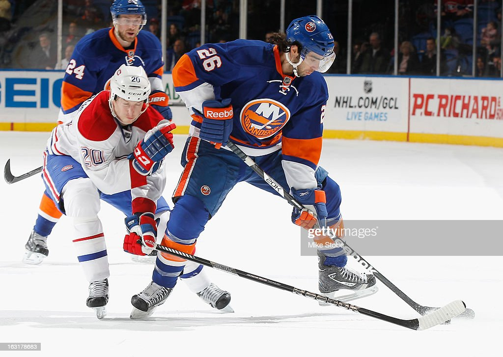 Matt Moulson #26 of the New York Islanders protects the puck in front of Colby Armstrong #20 of the Montreal Canadiens at Nassau Veterans Memorial Coliseum on March 5, 2013 in Uniondale, New York. The Islanders defeated the Canadiens 6-3.