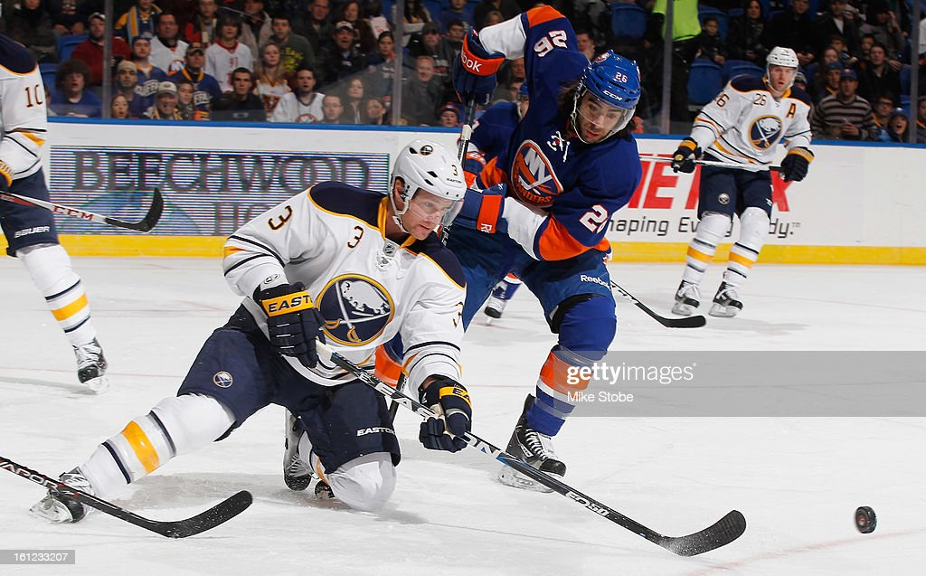 Matt Moulson #26 of the New York Islanders pursues the puck with Jordan Leopold #3 of the Buffalo Sabres in front of him at Nassau Veterans Memorial Coliseum on Febuary 9, 2013 in Uniondale, New York.