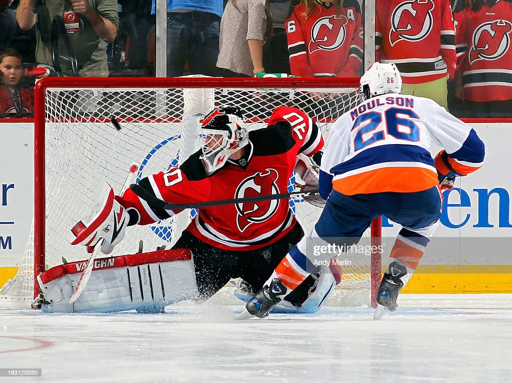 Matt Moulson of the New York Islanders puts the puck past Martin Brodeur of the New Jersey Devils for the game deciding goal in the shootout during...