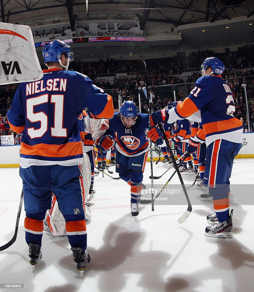 Matt Moulson #26 of the New York Islanders skates through the line of players after being named one of the stars of the game following a 4-1 victory over the Edmonton Oilers at the Nassau Veterans Memorial Coliseum on December 31, 2011 in Uniondale, New York.