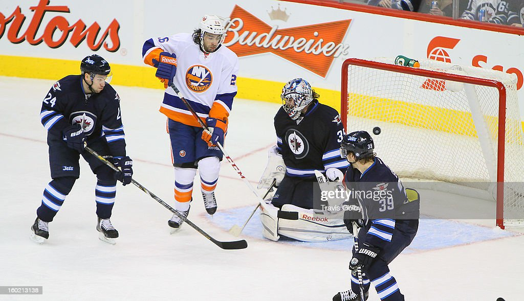 <a gi-track='captionPersonalityLinkClicked' href=/galleries/search?phrase=Matt+Moulson&family=editorial&specificpeople=3365493 ng-click='$event.stopPropagation()'>Matt Moulson</a> #26 of the New York Islanders tips the puck past goaltender <a gi-track='captionPersonalityLinkClicked' href=/galleries/search?phrase=Al+Montoya&family=editorial&specificpeople=213916 ng-click='$event.stopPropagation()'>Al Montoya</a> #35 of the Winnipeg Jets as defensemen Grant Clitsome #24 and <a gi-track='captionPersonalityLinkClicked' href=/galleries/search?phrase=Tobias+Enstrom&family=editorial&specificpeople=2538468 ng-click='$event.stopPropagation()'>Tobias Enstrom</a> #39 look on during third period action at the MTS Centre on January 27, 2013 in Winnipeg, Manitoba, Canada.
