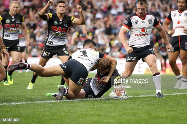 Matt Moylan of the Panthers scores a try under pressure from Roger TuivasaSheck of the Warriors during the round 10 NRL match between the Penrith...