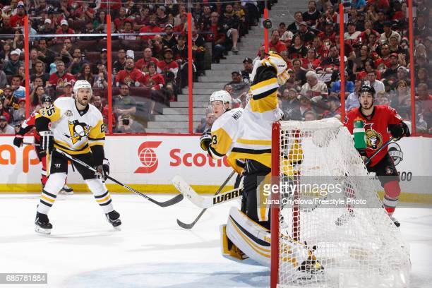 Matt Murray of the Pittsburgh Penguins deflects the puck over his glove as teammates Ron Hainsey and Olli Maatta and JeanGabriel Pageau of the Ottawa...