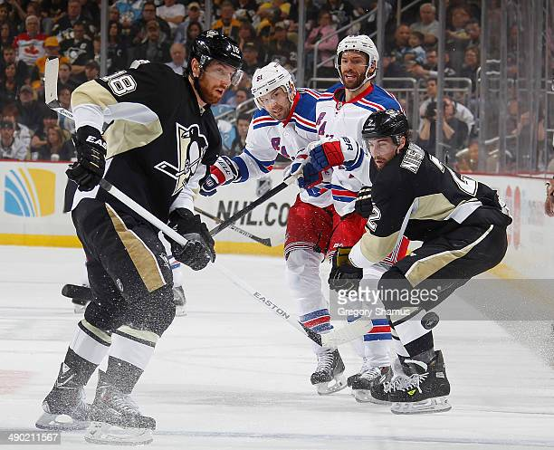 Matt Niskanen of the Pittsburgh Penguins watches the loose puck alongside Dominic Moore and Rick Nash of the New York Rangers in Game Seven of the...
