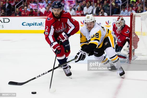 Matt Niskanen of the Washington Capitals and Jake Guentzel of the Pittsburgh Penguins battle for the puck in the second period at Capital One Arena...