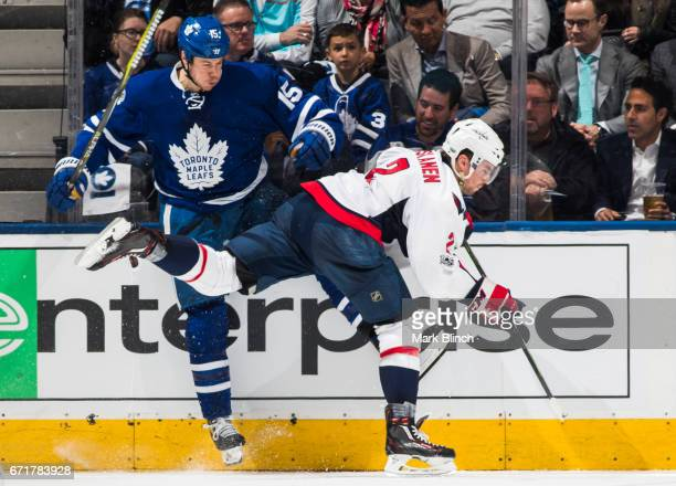Matt Niskanen of the Washington Capitals and Matt Martin of the Toronto Maple Leafs collide during the second period in Game Four of the Eastern...