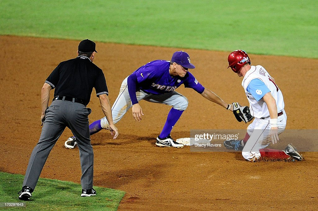 Matt Oberste #14 of the Oklahoma Sooners avoids a tag by JaCoby Jones #23 of the LSU Tigers during Game 2 of the NCAA baseball Super Regionals at Alex Box Stadium on June 8, 2013 in Baton Rouge, Louisiana.