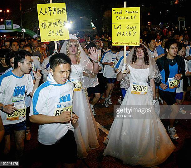 Matt Pearce and Adrian Smith wearing wedding dresses and holding placards run along with thousands of participants in the 10km Men's Open race of...