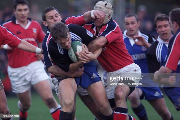 Matt Perry for Bath is tackled by Mike Mullins and Jason Holland for Munster at the Recreation Ground in Bath in the Heineken European Cup rugby match