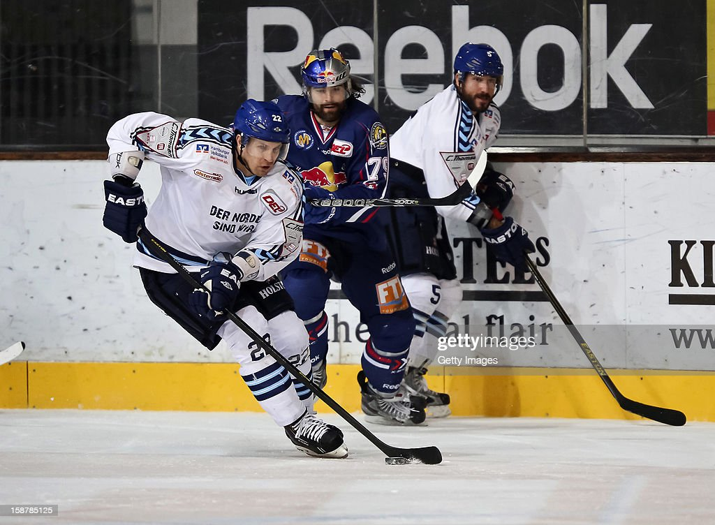 Matt Pettinger (L) of Hamburg Freezers in action with Ty Morris (C) of EHC Red Bull Munich in action during the DEL ice hockey game between EHC Red Bull Munich and Hamburg Freezer at Olympia Eishalle on December 28, 2012 in Munich, Germany.