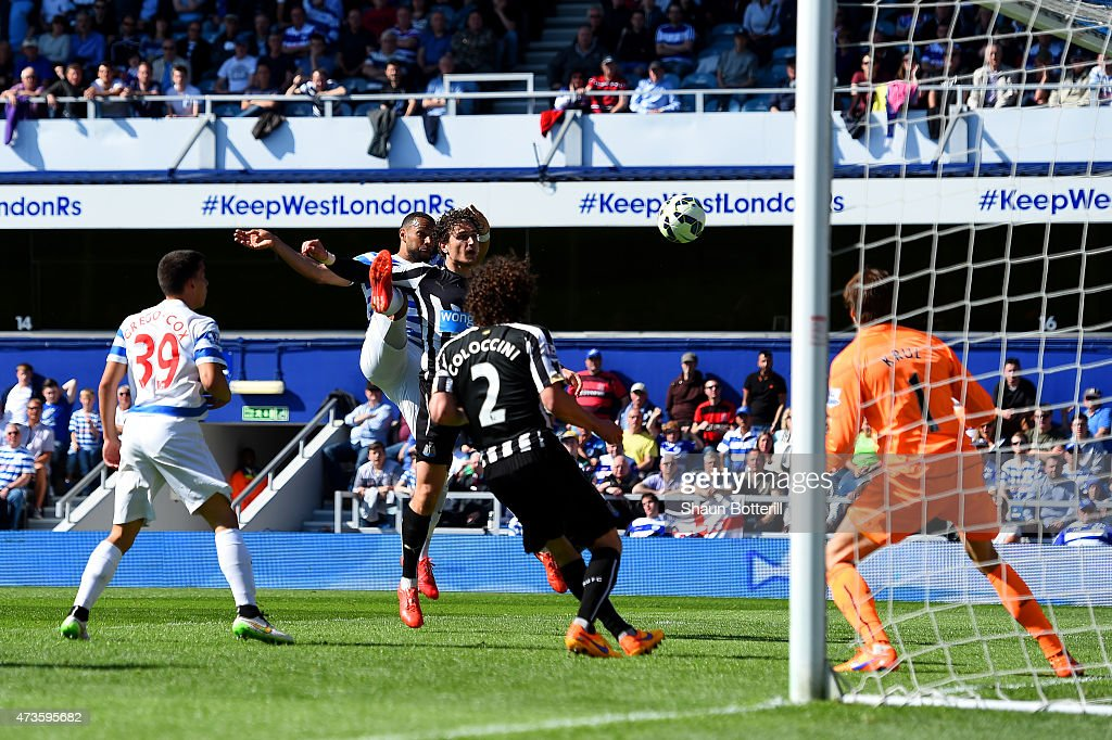 Matt Philips of QPR scores their first goal under pressure from Fabricio Coloccini of Newcastle United during the Barclays Premier League match between Queens Park Rangers and Newcastle United at Loftus Road on May 16, 2015 in London, England.