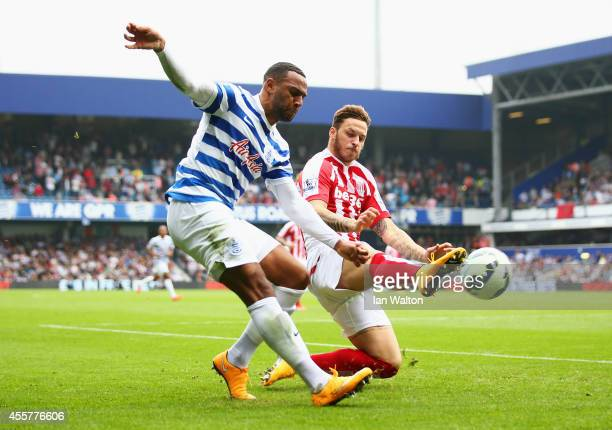 Matt Phillips of QPR is challenged by Marko Arnautovic of Stoke City during the Barclays Premier League match between Queens Park Rangers and Stoke...
