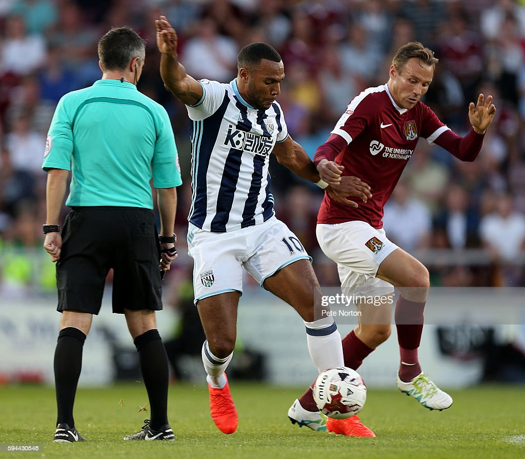 Matt Phillips of West Bromwich Albion controls the ball under pressure from Matt Taylor of Northampton Town as referee Darren Bond looks on during...