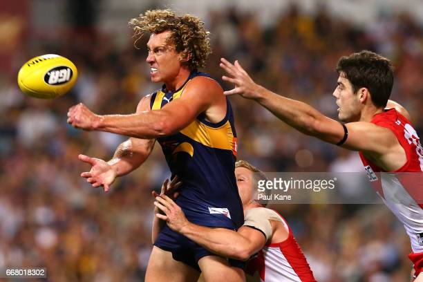 Matt Priddis of the Eagles gets his handball away while being tackled by Daniel Hannebery of the Swans during the round four AFL match between the...