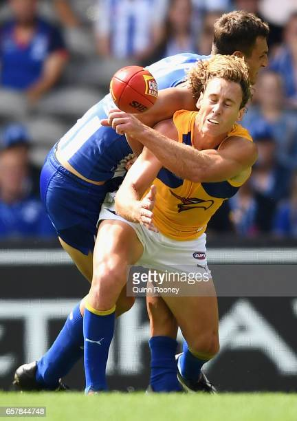 Matt Priddis of the Eagles handballs whilst being tackled by Braydon Preuss of the Kangaroos during the round one AFL match between the North...