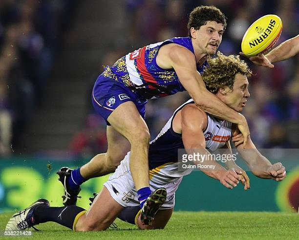 Matt Priddis of the Eagles handballs whilst being tackled by Tom Liberatore of the Bulldogs during the round 11 AFL match between the Western...