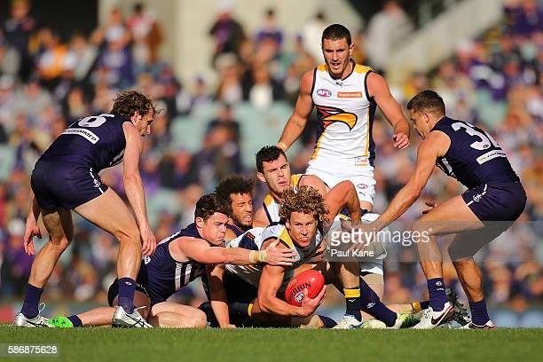Matt Priddis of the Eagles looks to handball while being tackled by Lachie Neale and Zac Clarke of the Dockers during the round 20 AFL match between...