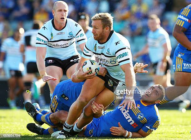 Matt Prior of the Sharks is tackled during the round 25 NRL match between the Parramatta Eels and the Cronulla Sharks at Pirtek Stadium on August 29...