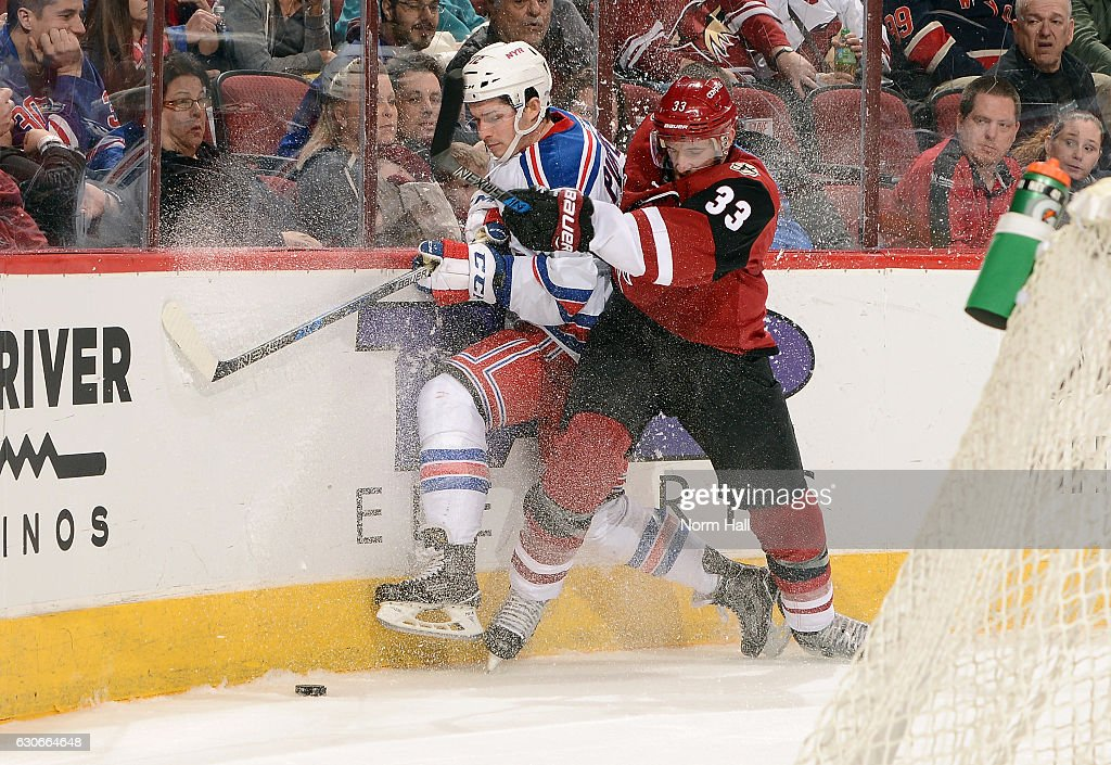 Matt Puempel #12 of the New York Rangers is checked by Alex Goligoski #33 of the Arizona Coyotes during the third period at Gila River Arena on December 29, 2016 in Glendale, Arizona. Puempel had a hat trick in the Rangers 6-3 victory over the Coyotes.