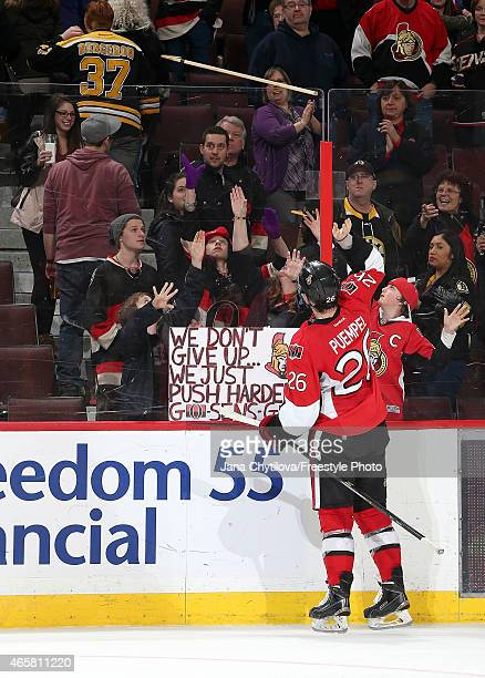 Matt Puempel of the Ottawa Senators throws his stick over the glass to a fan after being named the third star of the game against the Boston Bruins...