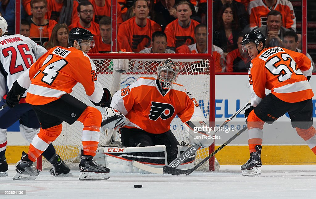 Matt Read and Nick Cousins of the Philadelphia Flyers attempt to clear the loose puck in front of goaltender Steve Mason against the Washington...