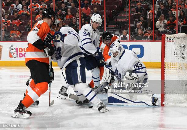 Matt Read and Sean Couturier of the Philadelphia Flyers battle for the puck in front of the net against Connor Brown Auston Matthews and Curtis...