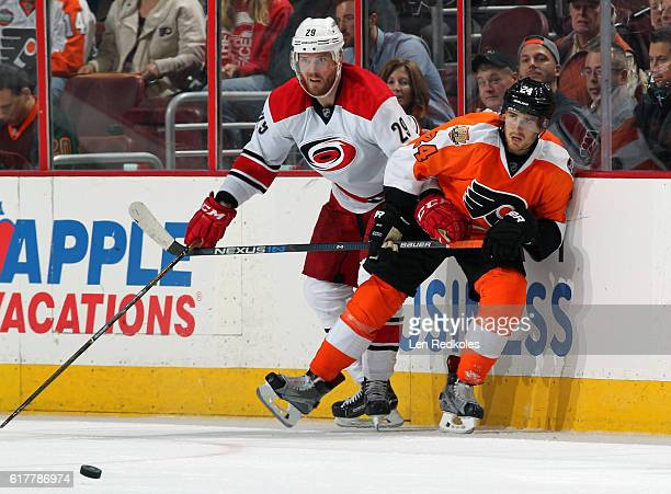 Matt Read of the Philadelphia Flyers battles along the boards for the loose puck against Bryan Bickell of the Carolina Hurricanes on October 22 2016...