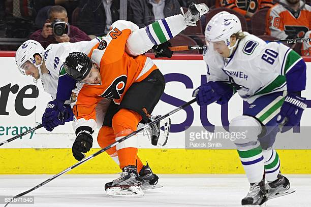 Matt Read of the Philadelphia Flyers bodychecks Jayson Megna of the Vancouver Canucks during the first period at Wells Fargo Center on January 12...