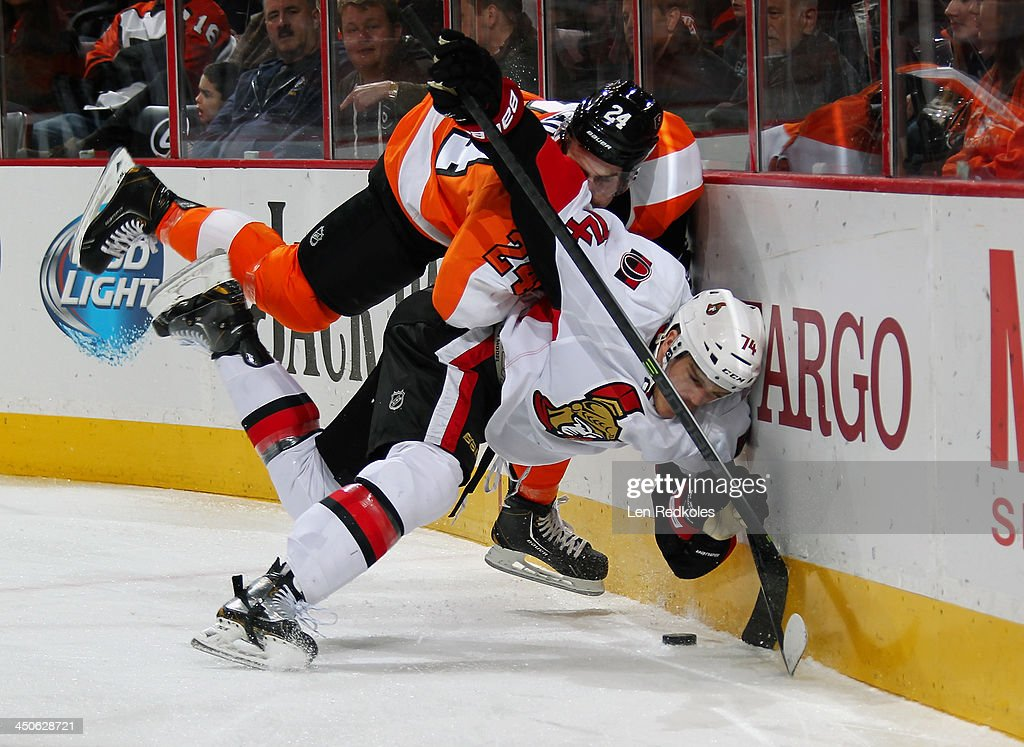 Matt Read #24 of the Philadelphia Flyers collides with Mark Borowiecki #74 of the Ottawa Senators along the boards while battling for the loose puck on November 19, 2013 at the Wells Fargo Center in Philadelphia, Pennsylvania.