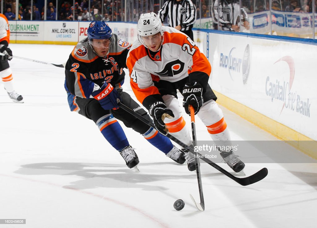 Matt Read of the Philadelphia Flyers controls the puck in front of Mark Streit of the New York Islanders at Nassau Veterans Memorial Coliseum on...